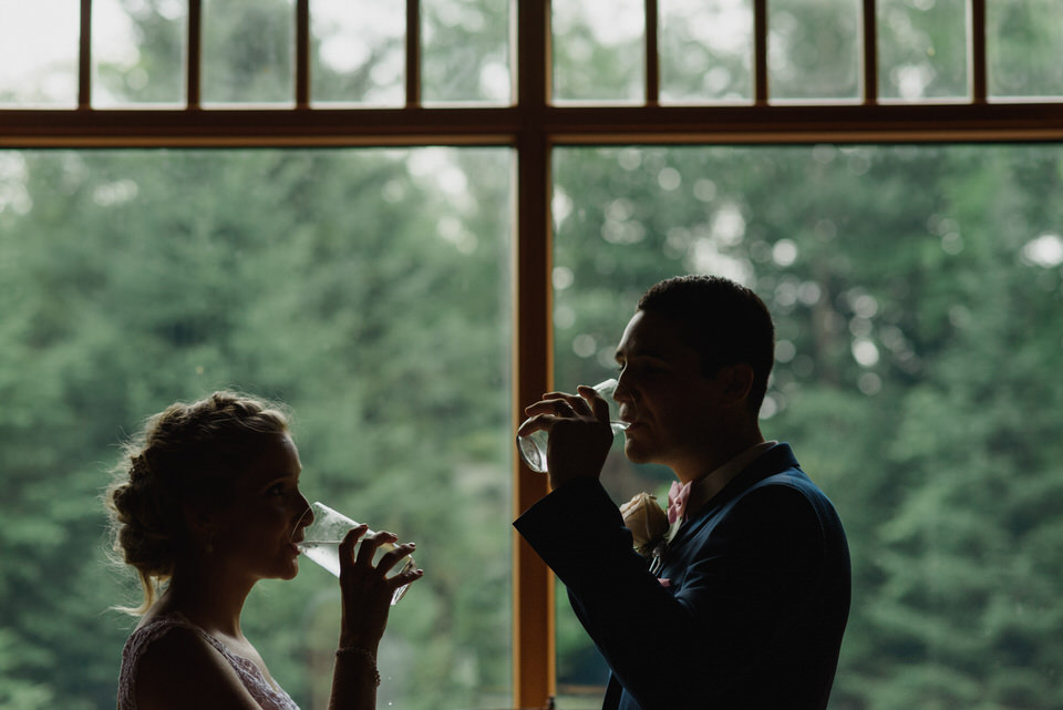 Silhouette wedding couple drinking in front of window with view of pine forest