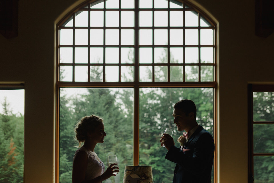 Silhouette of wedding couple drinking water in rustic cabin