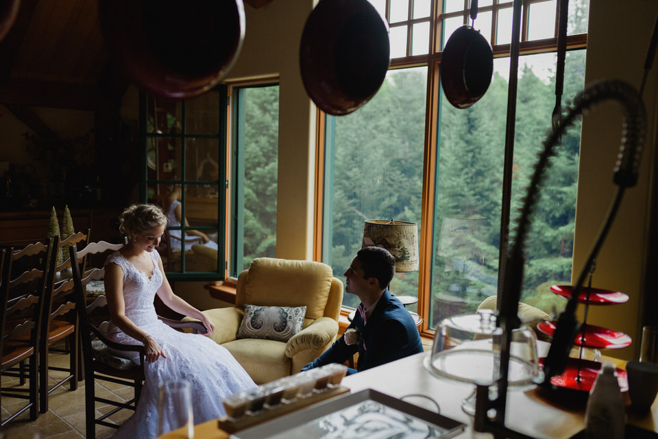 Bride and groom sitting inside rustic cabin