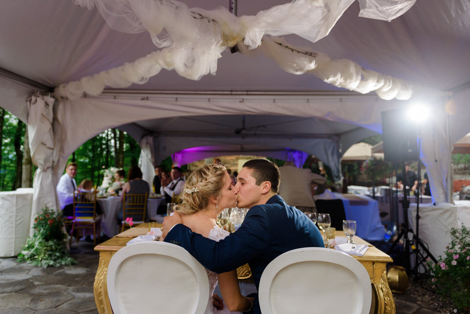 Bride and groom kissing at wedding reception under tent