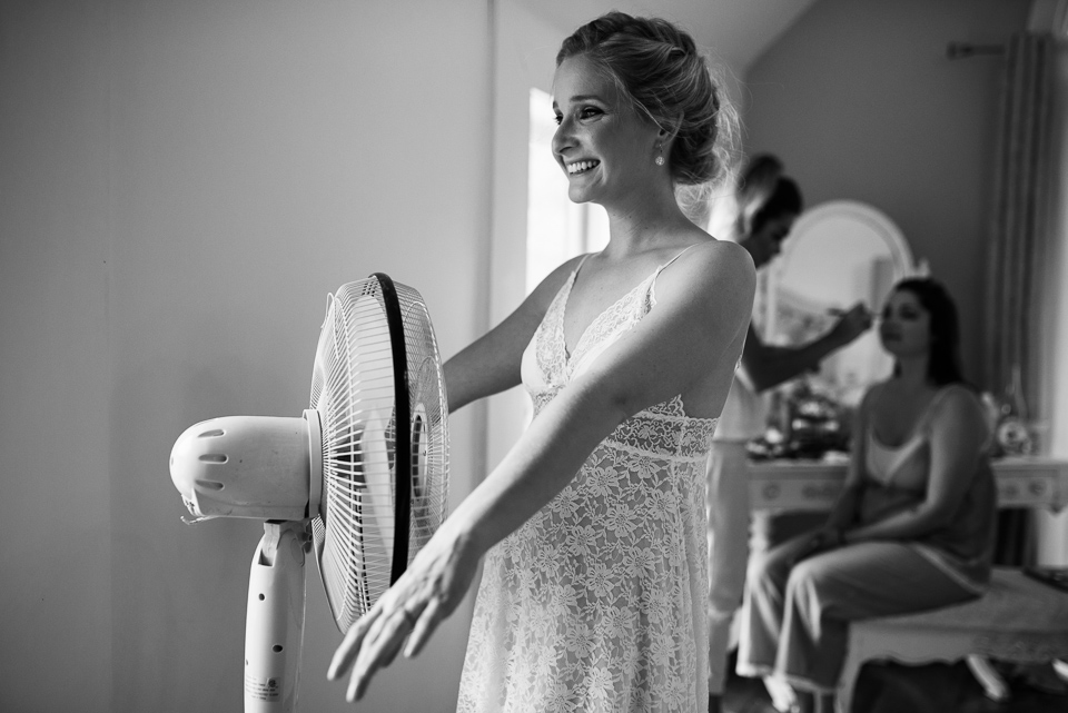 Black and white photo of bride cooling off in front of a fan