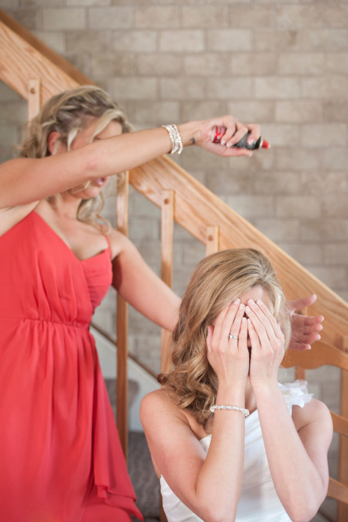Bridesmaid hairspraying her sister