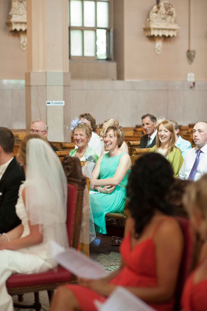 Wedding guests laughing during ceremony