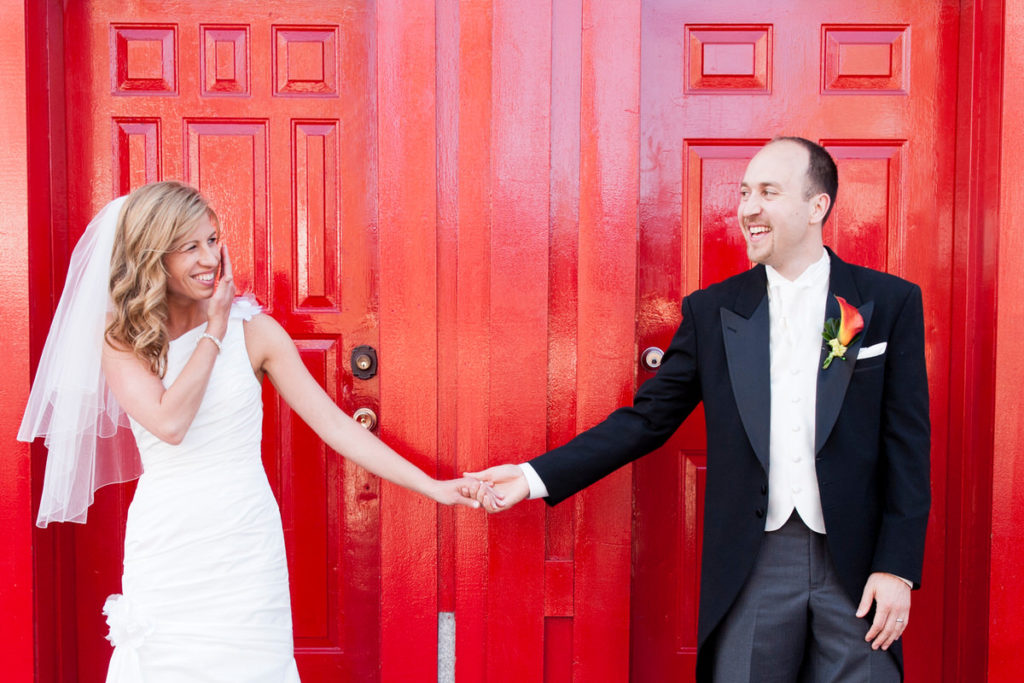 Bride and groom taking a picture in front of a red door