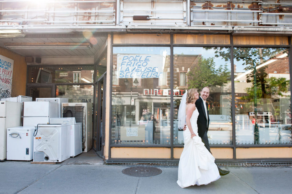 Wedding couple walking by a rundown appliance store