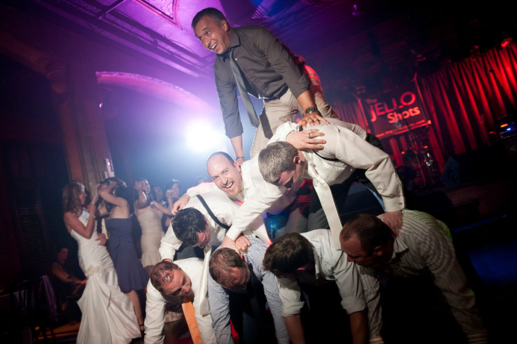 Wedding guests and groom forming a pyramid