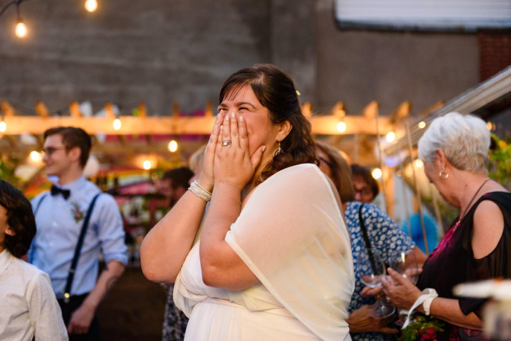 Bride with hands over face laughing during speech