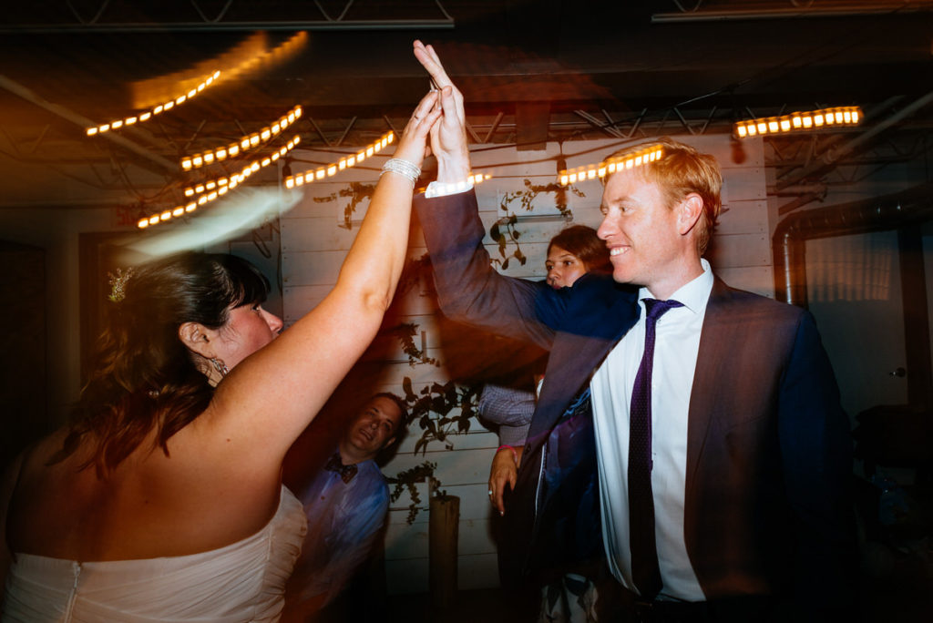 Bride high fiving her friend during wedding night