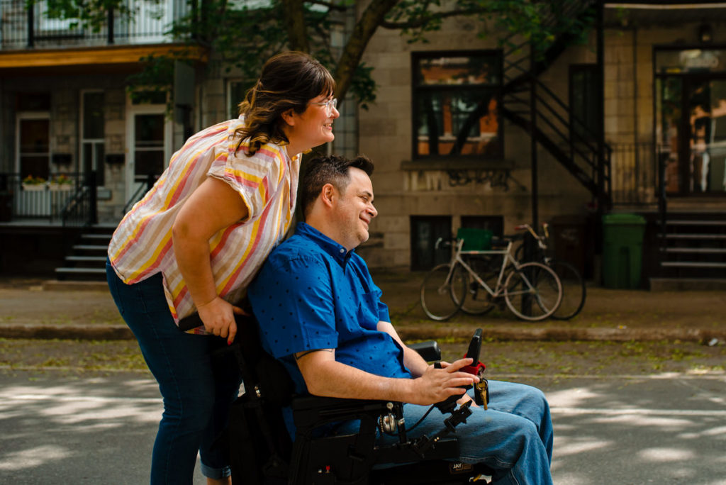 Woman riding on the back of her fiancé's wheelchair
