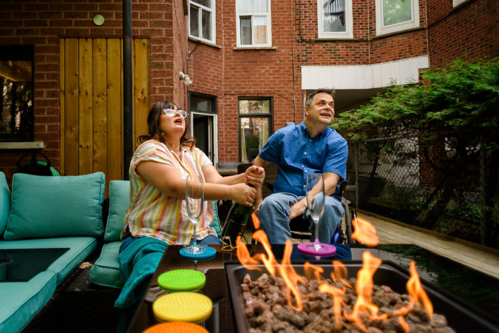 Woman popping champagne in front of a fire pit in backyard