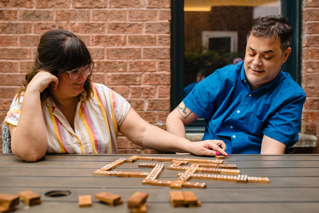 At-home engagement photo of couple playing dominoes