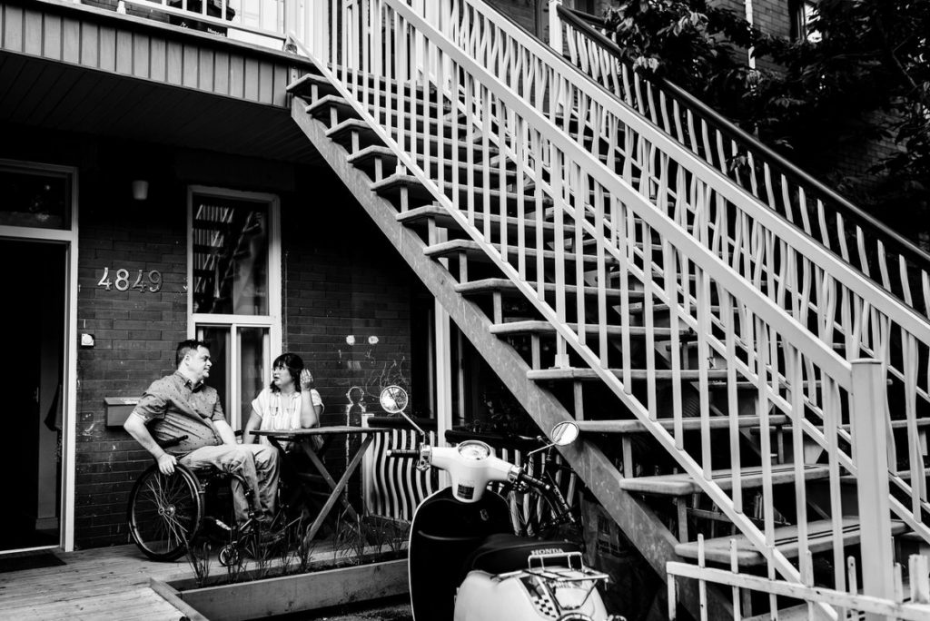 At-home engagement photo at their front porch patio table
