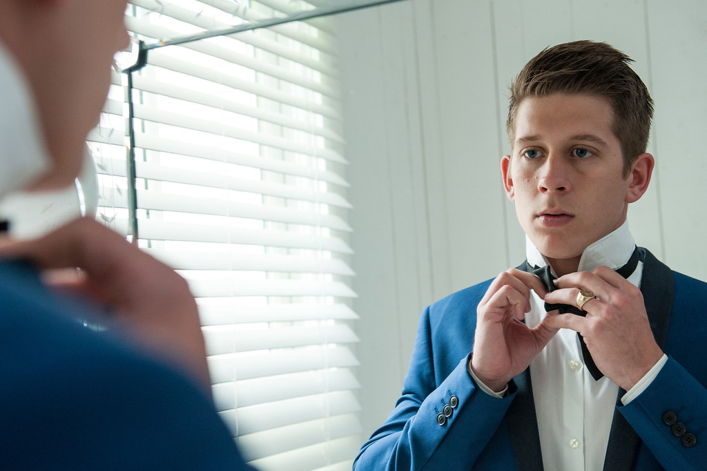 Groom tying his bow tie in mirror