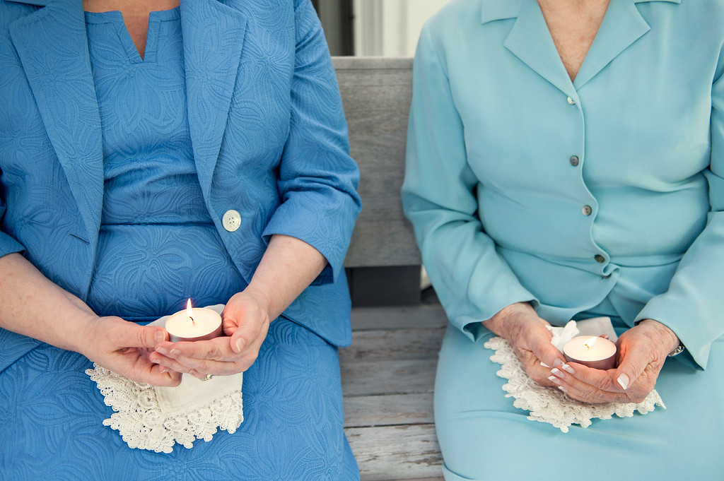 Grandmothers holding a candle and wedding handkerchiefs