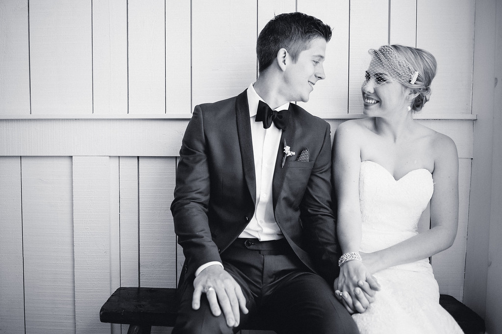 Bride and groom sitting on wooden bench inside old period home in Eastern Townships