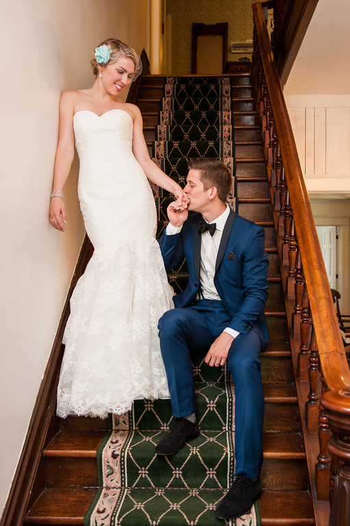 Groom sitting on staircase and kissing bride's hand