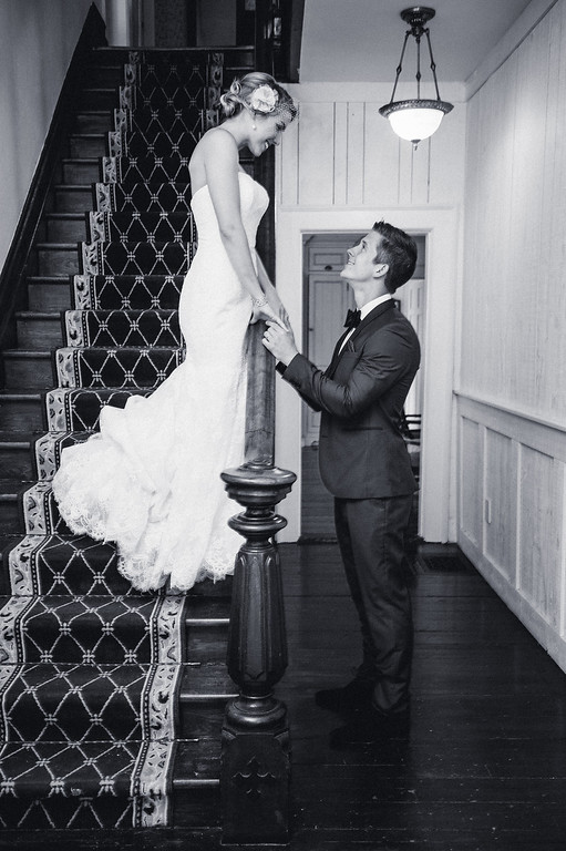 Bride standing on stairs and holding hands with groom below