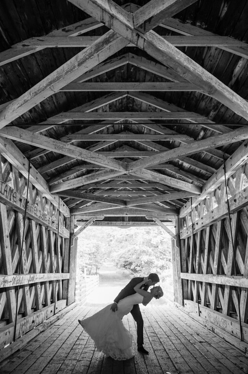 Wedding couple in silhouette under covered bridge near Fitch Bay