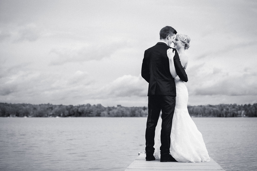 Bride and groom on dock at Fitch Bay