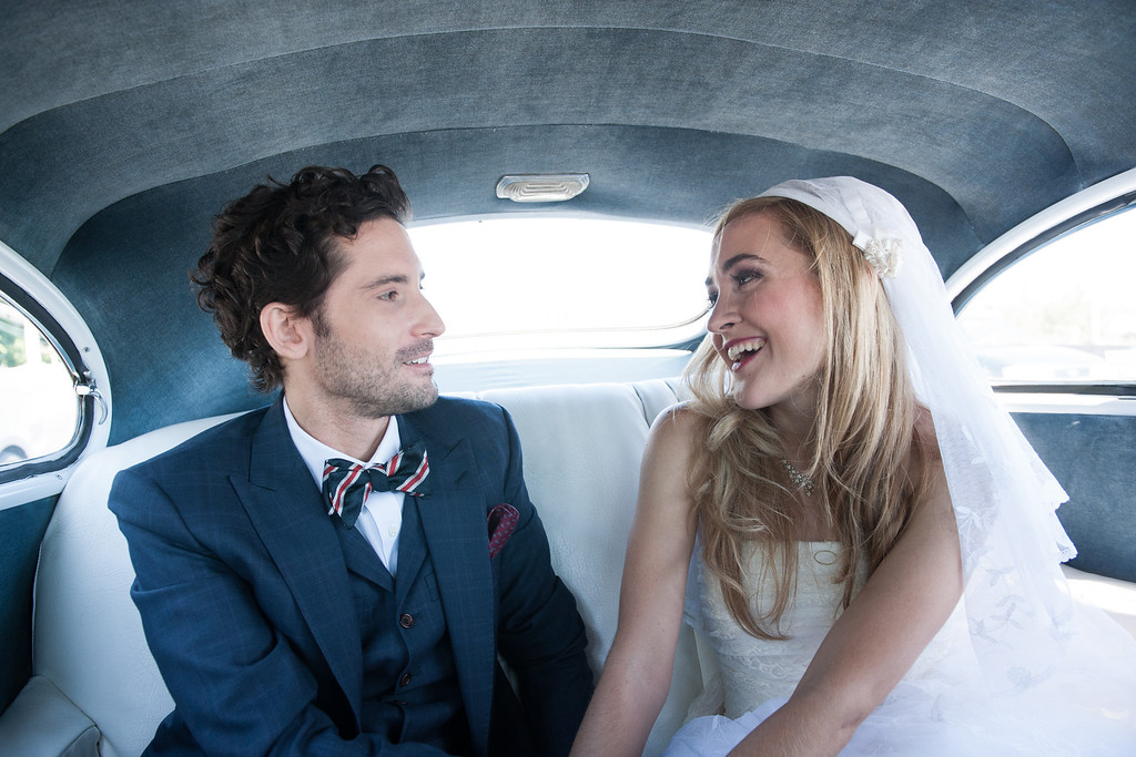 Wedding couple in vintage car on way to wedding