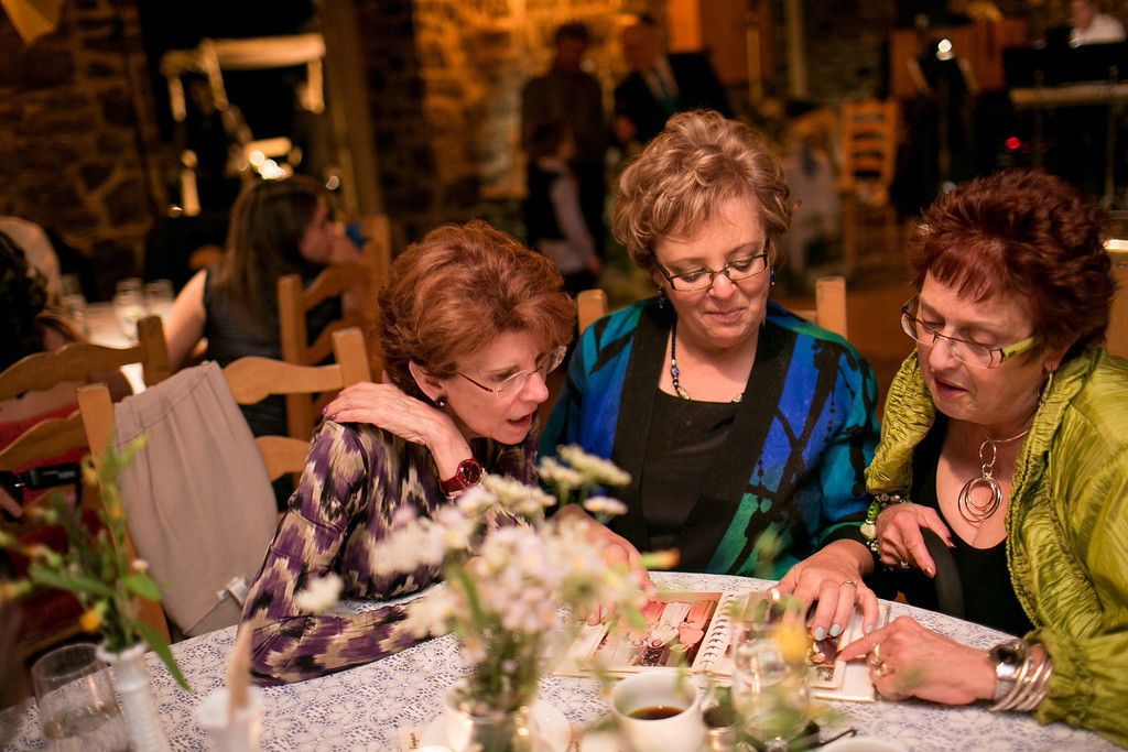 Family members looking at old wedding albums during reception
