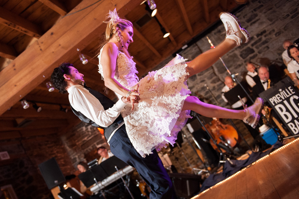 Wedding couple doing a jump move while swing dancing